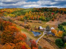 a-barn-nestled-in-a-valley-during-fall