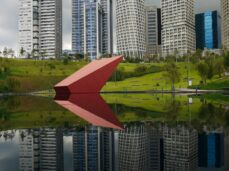 red-umbrella-near-body-of-water-and-city-buildings